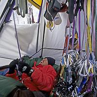 BAFFIN ISLAND, Nunavut, Canada. A sleepy Mark Synnott belays a climber from inside his Portaledge, high on Great Sail Peak, an Arctic big wall climb.