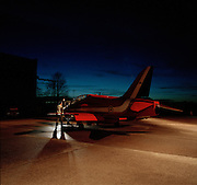 A red Hawk jet aircraft belonging to the elite 'Red Arrows', Britain's prestigious Royal Air Force aerobatic team, is parked outside a nearby hangar on the concrete 'apron' (where aircraft park) at the squadron's headquarters at RAF Scampton, Loncolnshire. A member of the team's support ground crew (the Blues because of their distinctive blue overalls worn at summer air shows) prepare to refuel as the last daylight fades and artificial light from the hangar illuminates the scene. Their winter training schedule is both rigorous on the aircraft and demanding on the pilots who will typically fly up to six times a day in preparation of the forthcoming summer when they display at 90-plus air shows. After the day's flying, the engineers' night shift arrive to service and maintain the aging fleet of 11 aircraft. .