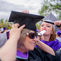 052315       Cable Hoover<br /> <br /> Nova Pino, right, and Sarah Borbon, left, help their teacher Tracy Welles untangle her tassel on a windy afternoon before the Miyamura High School graduation Saturday at Public School Stadium.