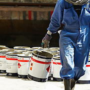 a worker carrying a tin across a ship yard