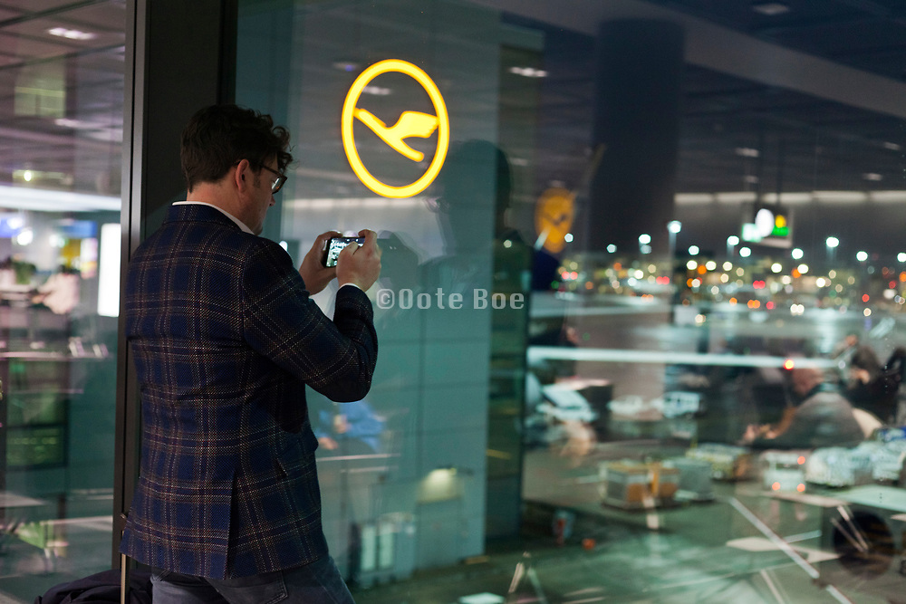 departure terminal with person photographing waiting airplane at Frankfurt airport