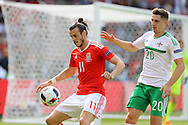 Gareth Bale of Wales shields the ball from Craig Cathcart of Northern Ireland. UEFA Euro 2016, last 16 , Wales v Northern Ireland at the Parc des Princes in Paris, France on Saturday 25th June 2016, pic by  Andrew Orchard, Andrew Orchard sports photography.