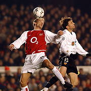 Arsenal's Dennis Bergkamp jumps with Valencia's Carboni