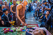 27 JANUARY 2014 - BANGKOK, THAILAND: A Buddhist monk participates in the bathing rites for anti-government leader Suthin Taratin at Wat Sommanat Rajavaravihara in Bangkok. In Thai tradition, after death a bathing ceremony takes place in which relatives and friends pour water over one hand of the deceased. Suthin was a core leader of the People's Democratic Force to Overthrow Thaksinism (Pefot), one of several organizations leading protests against the elected government of Thai Prime Minister Yingluck Shinawatra. He was murdered Sunday, Jan. 28, while he was leading a rally to prevent voters from reaching a polling center in the Bang Na district of Bangkok.     PHOTO BY JACK KURTZ