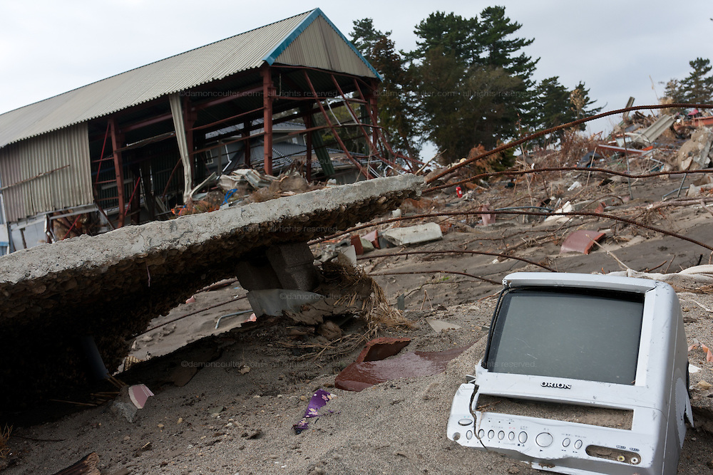 A TV set lies half buried in the mud of the ruined landscape in Shimo Masuda near Sendai airport. Residents had 30 minutes to flee the tsunami after a magnitude 9 earthquake struck off the coast on March 11th leveling the town killing large numbers of people. Shimo Masuda, Sendai, Miyagi, Japan. Wednesday May 4th 2011