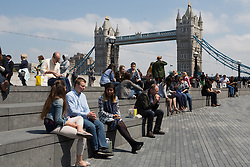 © Licensed to London News Pictures. 13/06/2016. LONDON, UK.  Office workers enjoying the sunny spring weather at lunchtime on the south bank in front of Tower Bridge.  Photo credit: Vickie Flores/LNP
