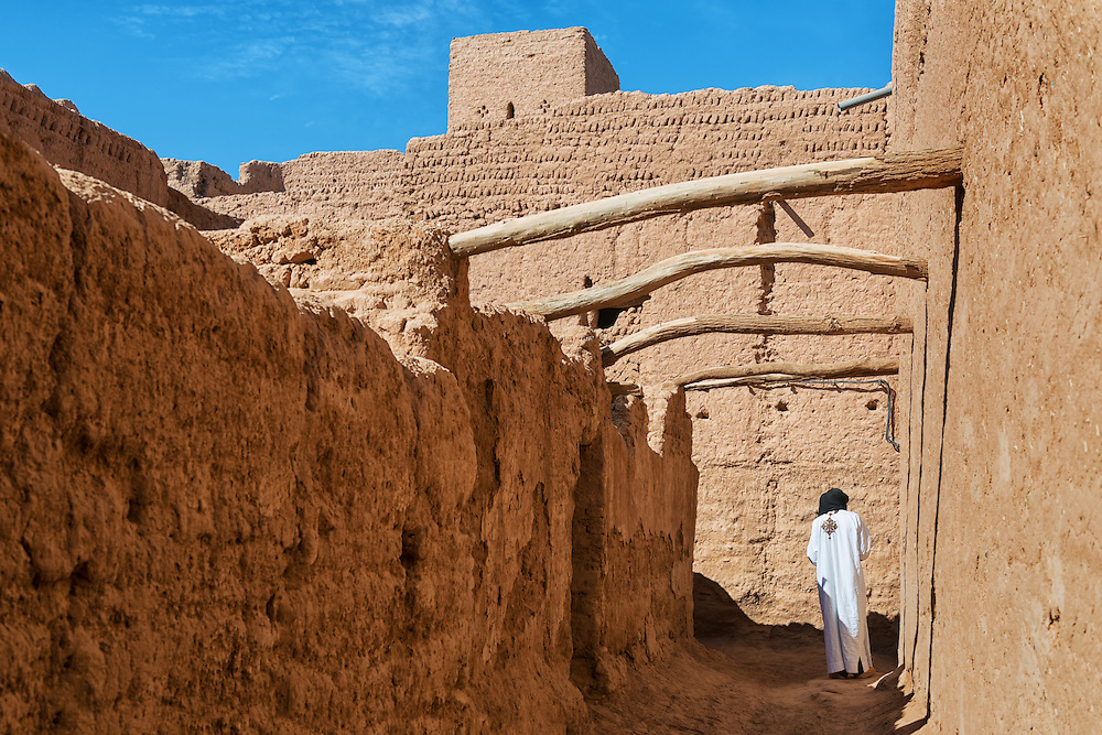 Traditional dressed man walks inside a kasbah in M'hamid, Morocco.