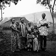 Mapendo Sakina, 20, far left, stands in her family's courtyard with her son, mother, other siblings, and her father, far right, who is a pastor in Kichanga. She was raped by two Rwandan rebels in 2007, and gave birth to a son. The father once disowned her after learning she was pregnant from the rapes, but accepted her after she gave a birth. He had her younger sister quit the school to pay for Mapendo's education and to help her become a math teacher.