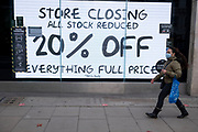 Storeclosing discounts as the national lockdown ends and the new three tier system of local coronavirus restrictions begins, shoppers head out to Oxford Street to catch up on shopping as non-essential shops like sport retailer Sports Direct are allowed to reopen on 2nd December 2020 in London, United Kingdom. Many shoppers wear face masks outside on the street as a precaution as there are so many people around.