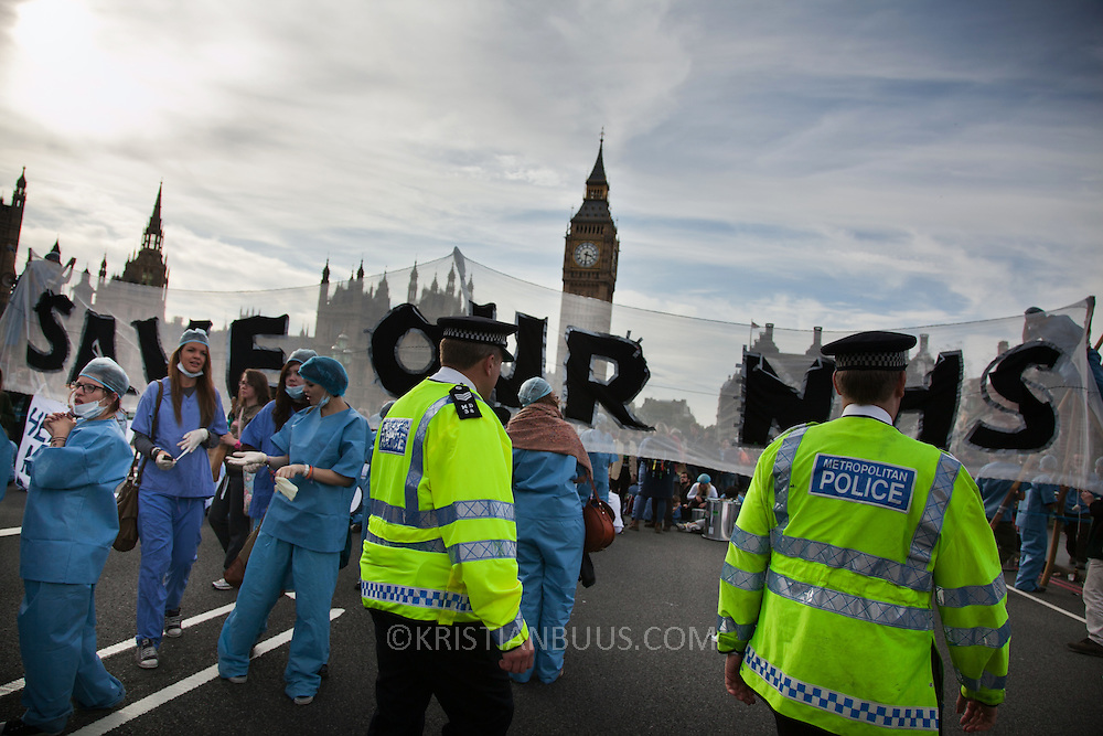 First sight of police on the bridge getting ready to clear the blockade..The Health and Care Bill has been passed by Parliament and is due to go to the House of Lords. In protest against the bill which aim to deconstruct and privatise large parts of the NHS UK Uncut activists together with health workers and trade unionists blocked the Westminster Bridge from 1pm til 5.30pm.
