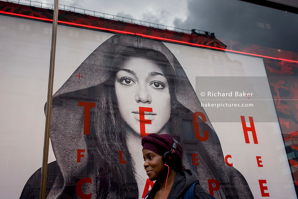 A young woman wearing heradphones walks beneath a large female model's face advertising Nike's Tech Fleeces.