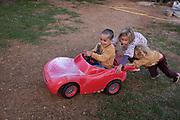 Young children pushing their brother in a toy car across a field of grass on a warm summers evening on the 5th October 2019 in the village of Terme, France.