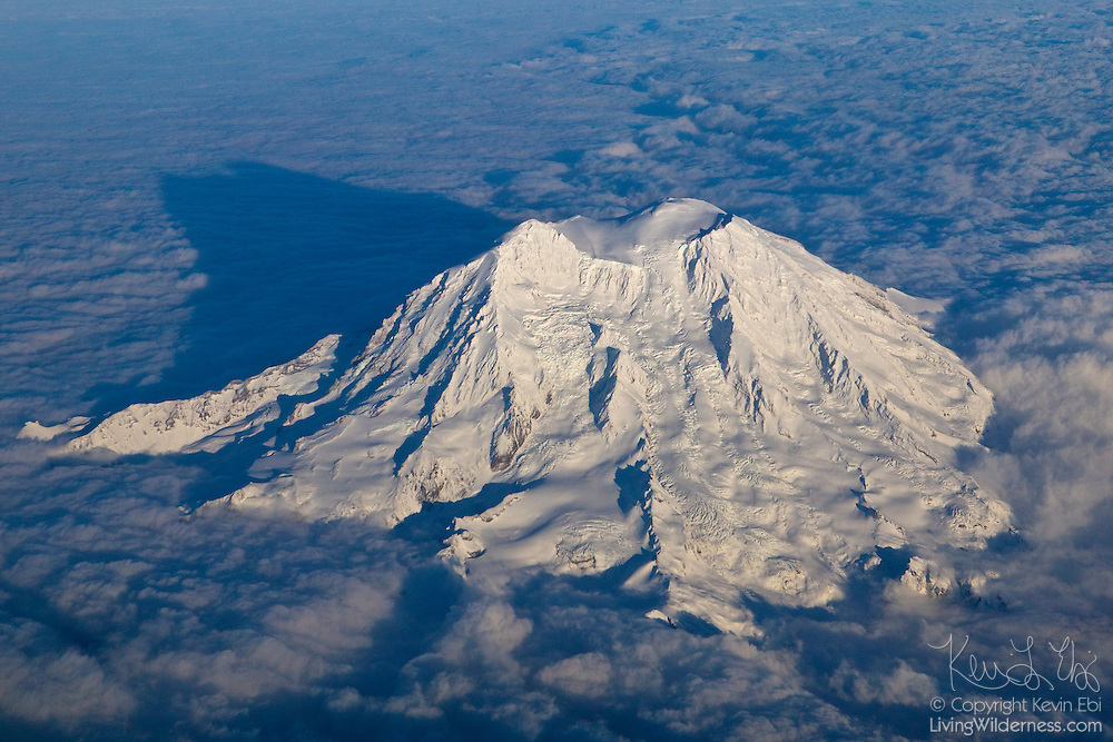 Mount Rainier, the tallest mountain in Washington state and the highest volcano in the Cascade Range, casts its own shadow on a thick cloud bank in this aerial view.