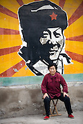 A woman sits in front of a mural depicting Lei Feng in a Hutong, or traditional Beijing neighborhood. Lei Feng was a soldier of the People's Liberation Army in the 1950-60's. He was characterized by propaganda as a selfless and modest figure after his death and consequently was an idol to many.....