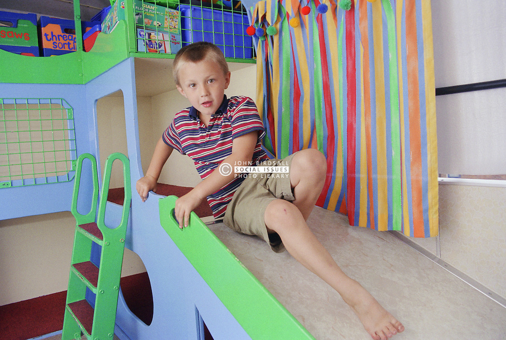 Young boy playing on slide in mobile playbus,