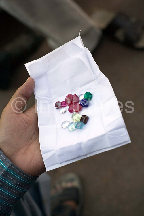 A man holds a handful of semi precious stones in an envelope on the street in the Johari bazaar, Jaipur, India