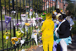 Group of people looking at the tribute flowers and cards attached to railings,