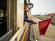 19 MARCH 2015 - AYUTTHAYA, AYUTTHAYA, THAILAND:  A conductorleans out of the window of the Ayutthaya to Bangkok third class train. The train line from Bangkok to Ayutthaya was the first rail built in Thailand and was opened in 1892. The State Railways of Thailand (SRT), established in 1890, operates 4,043 kilometers of meter gauge track that reaches most parts of Thailand. Much of the track and many of the trains are poorly maintained and trains frequently run late. Accidents and mishaps are also commonplace. Successive governments, including the current military government, have promised to upgrade rail services. The military government has signed contracts with China to upgrade rail lines and bring high speed rail to Thailand. Japan has also expressed an interest in working on the Thai train system. Third class train travel is very inexpensive. Many lines are free for Thai citizens and even lines that aren't free are only a few Baht. Many third class tickets are under the equivalent of a dollar. Third class cars are not air-conditioned.   PHOTO BY JACK KURTZ