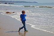Boy skipping rocks in ocean, El Matador State Beach, Malibu, Los Angeles County, California (MR)