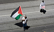 Pro-Palestinian protesters draped in flags and banners cross Swanston Street in Melbourne's CBD to show their support for Hamas in the fighting between Israel and Hamas in the Gaza Strip.