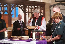 © Licensed to London News Pictures.  17/11/2013. THAME, UK. Reverend Colin Fletcher, Bishop of Dorchester, blesses flower petals collected from the congregation during the annual Road Deaths Memorial Service held in St Marys Church, Thame. 78 people were killed in traffic accidents in the Thames Valley Police area last year.  Photo credit: Cliff Hide/LNP