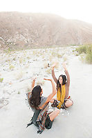 Two Wild Women in desert wilderness nature casting a magic spell into the winds.