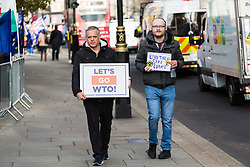 Two Leave Means Leave protester walk past Parliament towards College Green where major broadcasters have set up temporary studios, using the backdrop of the Houses of Parliament. London, January 14 2019.