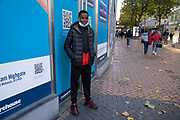 With local coronavirus lockdown measures in place and Birmingham currently set at 'Tier 2' or 'high', a young man wearing his face mask under his chin on New Street in the city centre poses for a picture on 26th October 2020 in Birmingham, United Kingdom. The three tier system in the UK has levels: 'medium', which includes the rule of six, 'high', which will cover most areas under current restrictions; and 'very high' for those areas with particularly high case numbers. Meanwhile there have been calls by politicians for a 'circuit breaker' complete lockdown to be announced to help the growing spread of the Covid-19 virus.