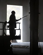 A worker sprays fireproofing material on a beam the maintenance area of the new Coach USA garage and headquarters under construction in Chester on Monday, Sept. 16, 2013.