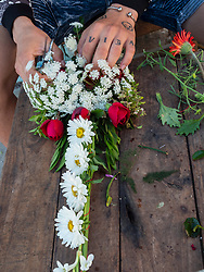 Caribbean, Cuba, Camaguey, hands creating floral cross for cemetary