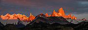 """Sunrise illuminates Cerro Fitz Roy (3405 meters or 11,171 feet elevation), seen from Mirador Condores near Los Glaciares National Park Visitor Center, in El Chalten in Santa Cruz Province, Argentina, Patagonia, South America. Monte Fitz Roy is also known as Cerro Chaltén, Cerro Fitz Roy, or Mount Fitz Roy. The first Europeans recorded as seeing Mount Fitz Roy were the Spanish explorer Antonio de Viedma and his companions, who in 1783 reached the shores of Viedma Lake. In 1877, Argentine explorer Francisco Moreno saw the mountain and named it Fitz Roy in honour of Robert FitzRoy who, as captain of HMS Beagle, had travelled up the Santa Cruz River in 1834 and charted large parts of the Patagonian coast. Mt Fitz Roy was first climbed in 1952. Cerro is a Spanish word meaning hill, while Chaltén comes from a Tehuelche word meaning """"smoking mountain"""", due to clouds that usually form around the peak. This image was stitched from multiple overlapping photos."""