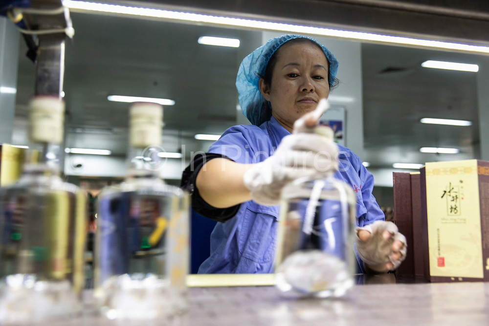Workers examine bottles of Shuijingfang baiju for flaws and defects before boxing them at the Yongxing baijiu distillery operated by Sichuan Swellfun Co., a unit of Diageo Plc in Chengdu, China, on Tuesday, Sept. 20, 2016. With less than 1 percent of baijiu, or white liquor, consumed abroad, Chinese distillers want to transform the fiery Chinese grain liquor into the new tequila for Americans and Europeans.