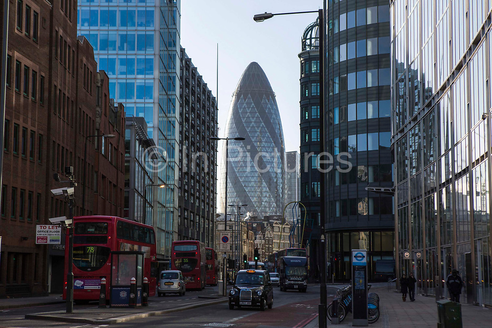 A view of the Gherkin building from Bishopsgate, London, United Kingdom.  A typical street scene in the City of London which includes the iconic hackney carriage, black taxi cab, and red double decker bus and Boris bikes, all part of Transport for London.