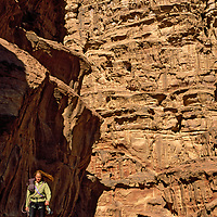 Rakabat Siq, Jebel Um Ishrin, Wadi Rum, Jordan. A rock climber approaches remote desert cliffs.