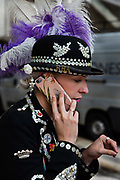 Pearly Princess on the mobile phone at the Pearly Kings and Queens Harvest Festival celebrations at Guildhall Yard. The annual event features early English entertainment including maypole dancing, Morris dancers and a marching band. The Chelsea pensioners & all the mayors of London take part in this traditional London event.<br /> The London tradition of the Pearly Kings and Queens began in 1875, by Henry Croft. Inspired by the local Costermongers, a close-knit group of market traders who looked after one another and were recognisable by buttons sewed onto their garments, Henry went out on the streets to collect money for charity, wearing a suit covered in pearl buttons to attract attention. When demand for his help became too much, Henry asked the Costermongers for assistance, many of whom became the first Pearly Families. Today, around 30 Pearly Families continue the tradition to raise money for various charities.