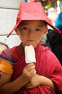 A very young novice Tibetan Buddhist monk eats some ice cream in Yushu, Tibet.