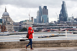 © Licensed to London News Pictures. 26/08/2015. London, UK. People crossing Waterloo Bridge during heavy rain in central London on Wednesday, August 26, 2015. Photo credit: Tolga Akmen/LNP