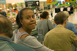 Group of Day Service users with learning disabilities coming down on the escalator to the supermarket accompanied by a Care Assistant,