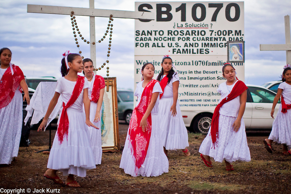 July 22 - PHOENIX, AZ: Folklorico dancers perform during a rosary service on a street corner in Phoenix, AZ. About 50 people gathered on a street corner in a Hispanic neighborhood in Phoenix, AZ, Thursday night to pray the rosary. They are members of a Catholic community that opposes Arizona's tough new immigration law, SB 1070, which requires local police officers to check the immigration status of people they suspect of being in the US illegally and requires legal immigrants in Arizona to carry their immigration documents with them at all times. Photo by Jack Kurtz