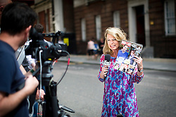 © London News Pictures. 20/07/2013. London based Fox News reporter Amy Kellogg holds up a copy of HELLO! magazine with pictured of The Duchess of Cambridge and Prince William on the front during a pice to camera outside the Lindo Wing entrance to  St Mary's Hospital in West London where The Duchess of Cambridge is expected to be admitted when she goes into labour. Photo credit: Ben Cawthra/LNP