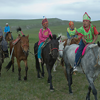 Young, costumed riders - some bareback- after a 20km race at a traditional naadam festival on a remote pass near Muren, Mongolia.