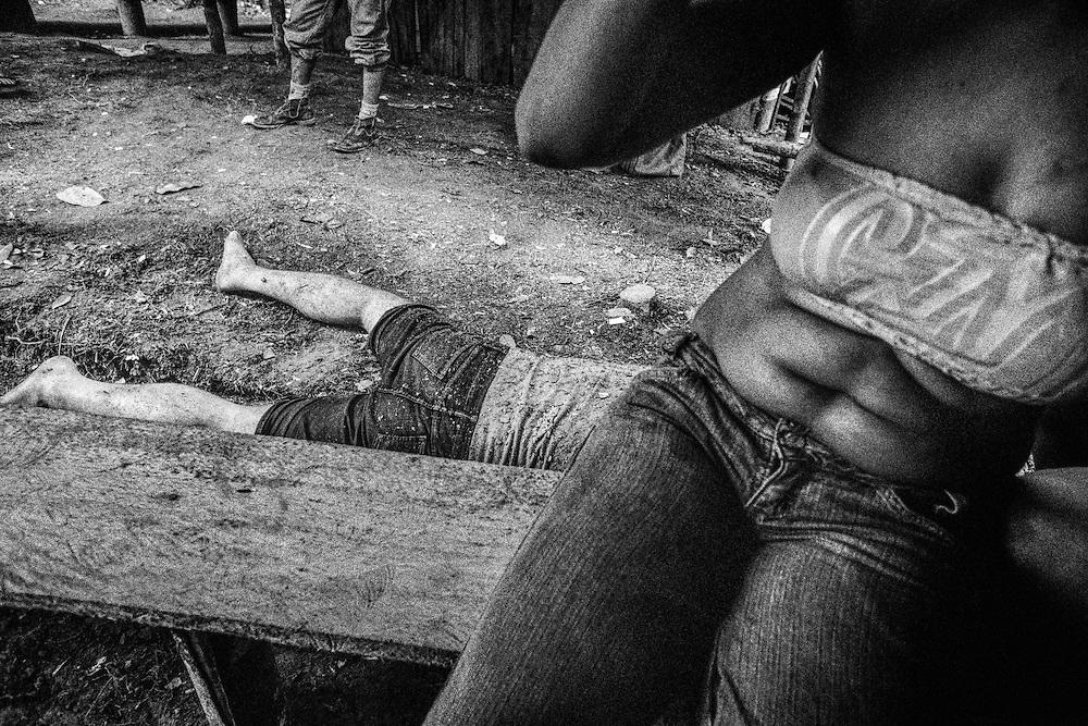 Brazil, Amazonas, Eldorado do Juma.<br /> <br /> Grota rica, curutela (camp de base).<br /> Eldorado do Juma est maintenant un bidonville de plastique noir et de misere croissante sur la rive du fleuve, qui attire les prospecteurs. Des centaines d'hommes y creusent la boue sur leurs petites parcelles delimitees par des branchages et des ficelles. A la fin du jour, les plus chanceux auront trouve quelques poussieres d'or, vendues ensuite 40 reals le gramme (14,5 euros) a Apui, 65km au nord. Les plus riches du coin sont ceux et celles qui cuisinent, nettoient ou divertissent les mineurs.<br /> Un mineur ivre dort a meme le sol alors qu'une jeune femme attend un compagnon.
