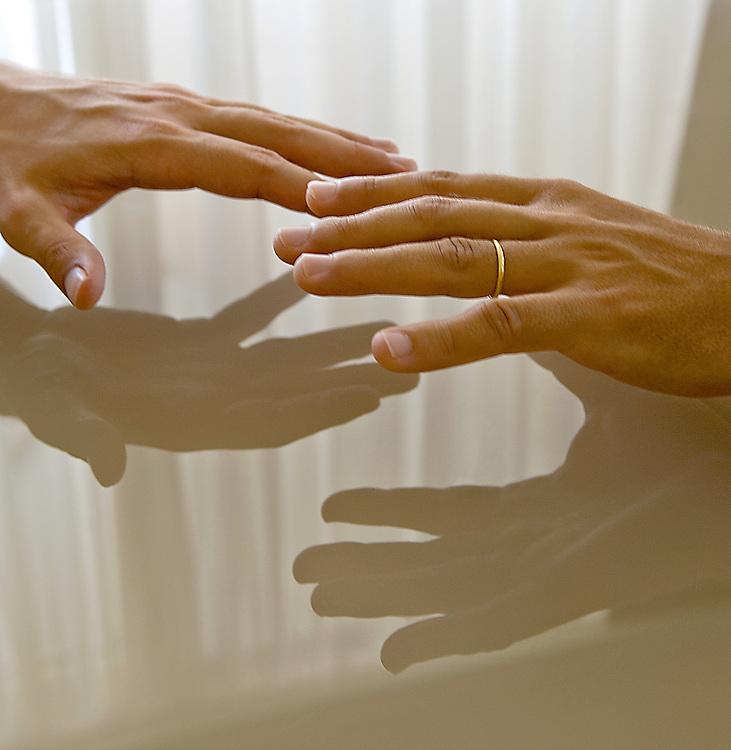 Deux mains d'hommes se reflétant sur une table vitrée.