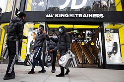 © Licensed to London News Pictures. 02/12/2020. London, UK. Shoppers depart a branch of JD sports on Oxford Street. Today England returns to tiered COVID restrictions following the end of the second national lockdown. Photo credit: George Cracknell Wright/LNP
