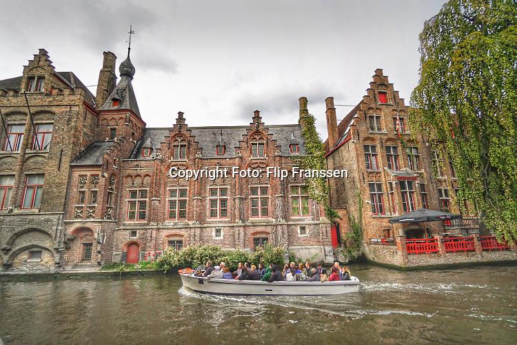 Belgie, Vlaanderen, Brugge, 9-9-2019Een rondvaartboot vol toeristen maakt een rondvaart door de oude stad . Brugge is een toeristische trekpleister .Foto: Flip Franssen