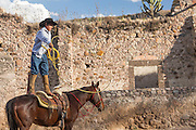 A Mexican charro or cowboy practices roping skills on his horse at a hacienda ranch in Alcocer, Mexico. The Charreada is a traditional Mexican form of rodeo and tests the skills of the cowboy at riding, roping and controlling cattle.