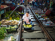 27 SEPTEMBER 2016 - BANGKOK, THAILAND: A woman sells limes in the market in the train station in Samut Songkhram. The train from Baen Laem to Samut Songkhram (Mae Khlong) recently resumed service. The 33 kilometer track was closed for repair for almost a year. In Samut Songkhram, the train passes over the market. Vendors pull their stands out of the way and people step out of the way as the train passes through the market. It is one of the most famous train stations in Thailand and has become an important tourist attraction in the community.     PHOTO BY JACK KURTZ