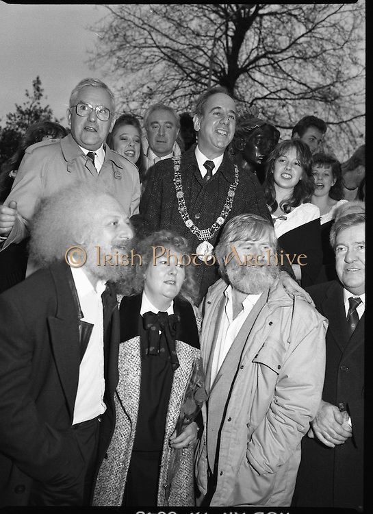 """Molly Malone Statue Unveiled. (R93)..1988..20.12.1988..12.20.1988..20th December 1988..""""Dublin's Fair City"""" received a millenniun gift to commemorate her most famous daughter, Molly Malone, when Jurys Hotel Group plc presented a specially commissioned sculpture to the people of Dublin. The sculpture was formally handed over by Michael McCarthy, MD,Jurys Hotel Group, to the Lord Mayor of Dublin, Councillor Ben Briscoe, TD, in an unveiling ceremony today at the corner of Grafton Street, Suffolk Street and Nassau Street..Molly Malone was created and fashioned in her traditional 17th century dress by Dublin born artist, Jeanne Rynhart, who was selected from a number of entries for the statue design, by the Dublin Millennium Board...'Dubliners' Eamon Campbell and John Sheehan are pictured with artist  Jeanne Rynhart at the statues' unveiling in Grafton Street. Lord Mayor Ben Briscoe and Michael McCarthy of Jurys are in the background."""