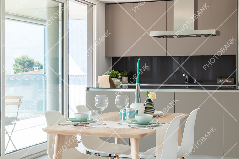 Detail of designer set table. Behind the modern designer kitchen with island. Nobody inside