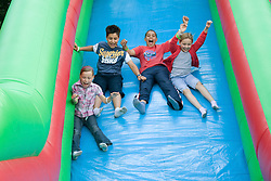 Group of children enjoying the big inflatable slide at a Parklife summer activities event,